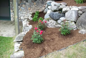 Landscaping job rock wall with addtion of flowers - Cutting Edge Caretaking